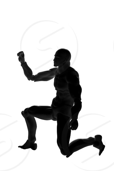 Silhouette of a man in a pose on his knee on a white background photo