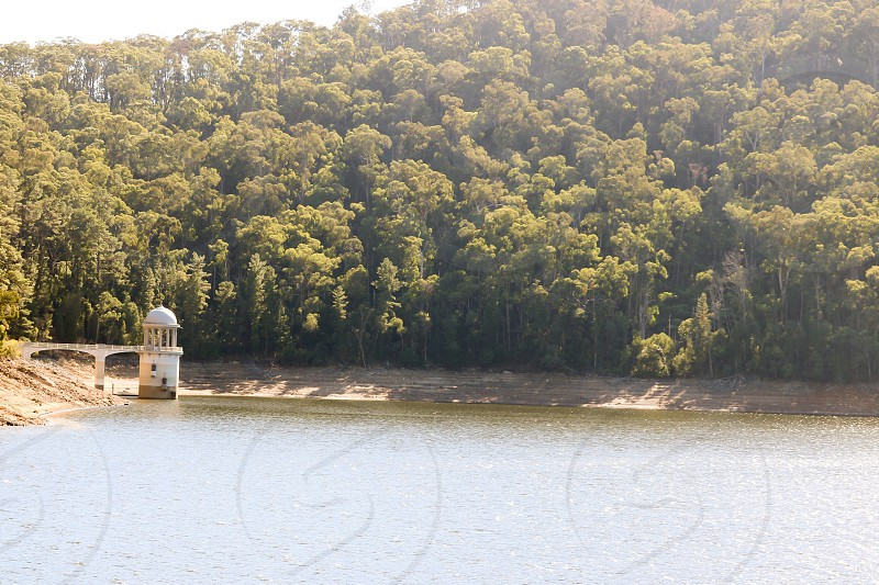 white watch tower on body of water surrounded with green trees photo