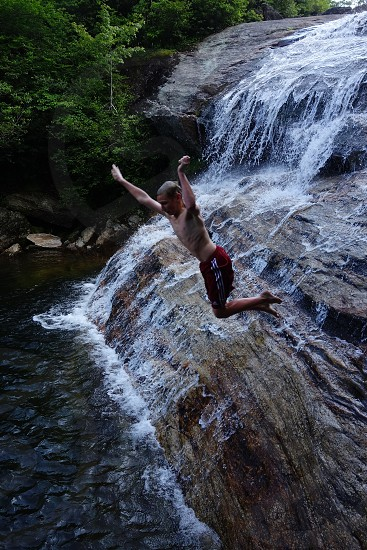 Kid jumping off waterfall photo
