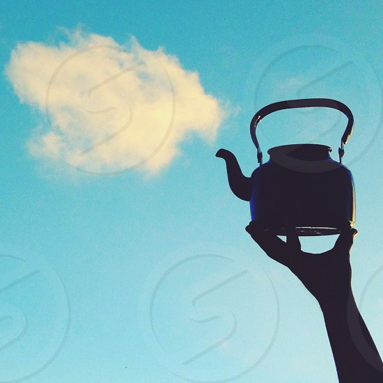 person lifting a steel kettle photo