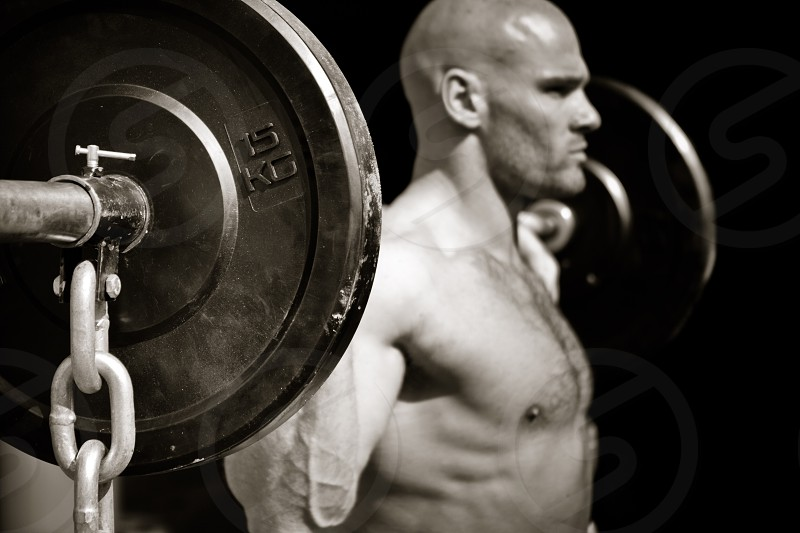 Black and white close up of man lifting weights. photo