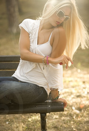 Thoughtful young blond woman sitting on the bench in park contemplating photo