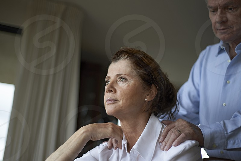 Elderly woman sitting at a table in her home with a mobile device looking upset and desperate with her husband standing behind her with his hands resting on her shoulder to comfort her and support her photo