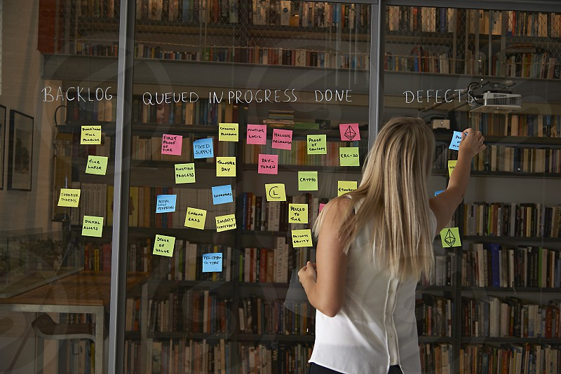 Young blonde female office worker organizing post-it notes on a glass partition for scheduling photo