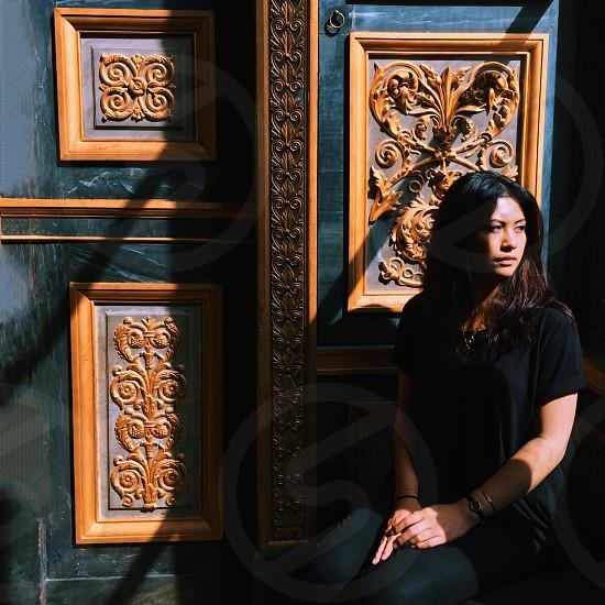 woman in black blouse sitting beside black wooden door photo