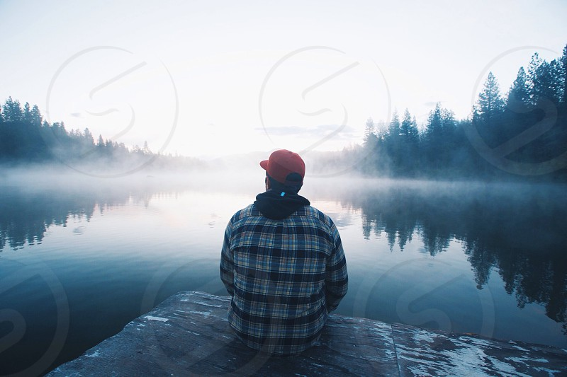 man in black white and blue plaid shirt and red fitted cap sitting on edge of dock staring at misty lake photo