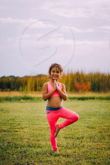 Little girl doing outdoor yoga. photo