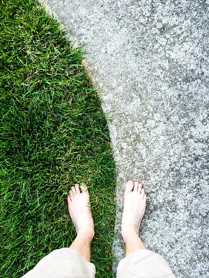 P.O.V of feet on grass and cement. photo