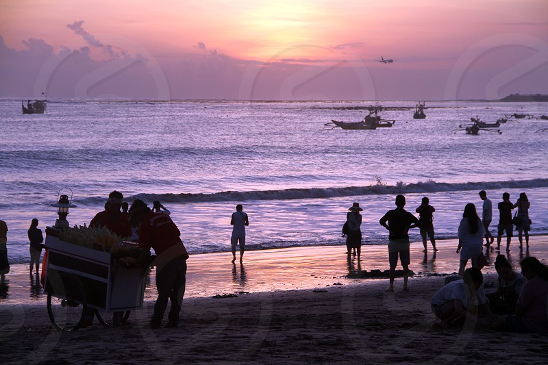 Silhouettes in a Bali beach - people food-trucks boats plane .... photo