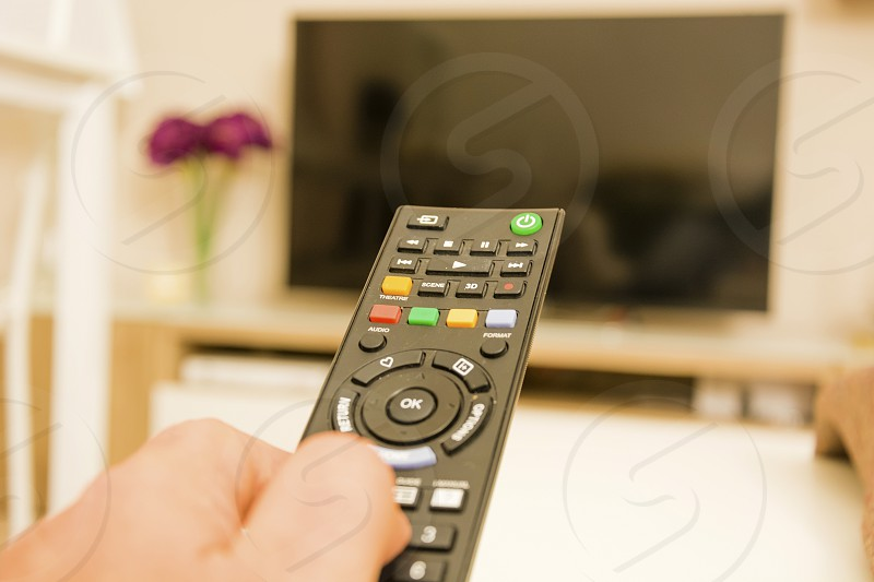 hand with tv remote control photo