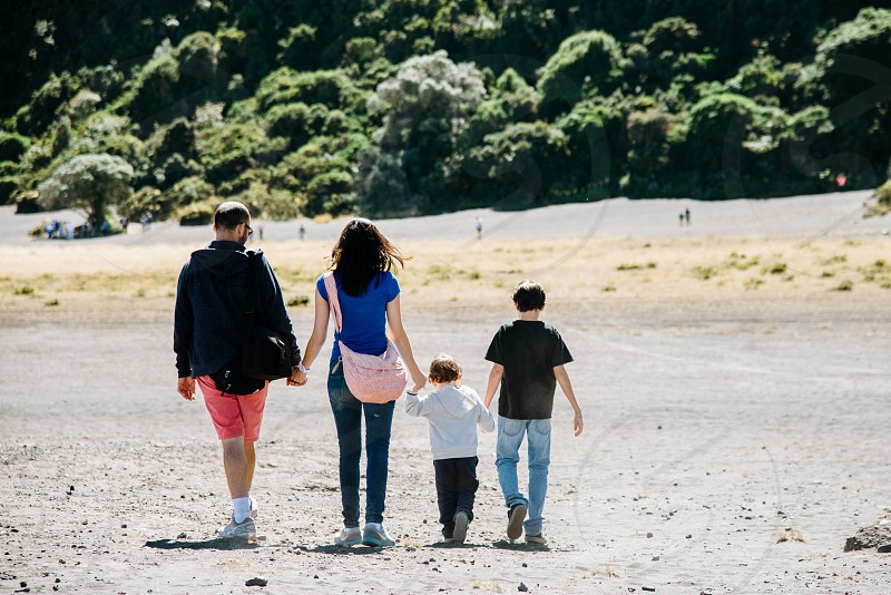 photo of man woman child and toddler walking while holding hands together during sunny day photo
