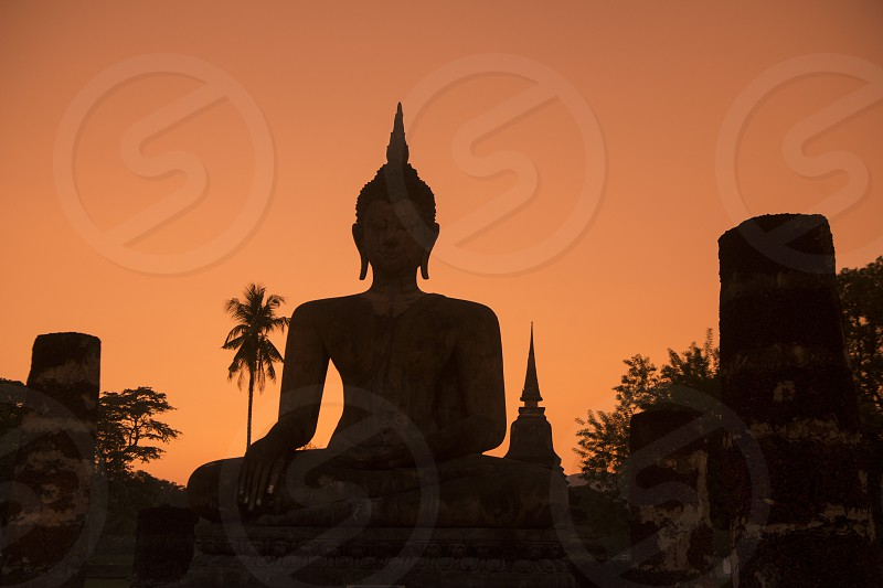 a Buddha statue at the Wat Mahathat Temple at the Historical Park in Sukhothai in the Provinz Sukhothai in Thailand.   Thailand Sukhothai November 2018 photo