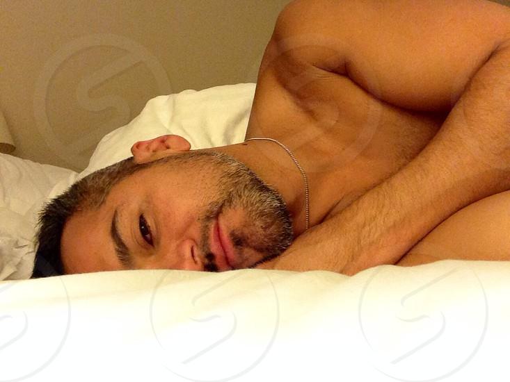 man lying on white bed photo