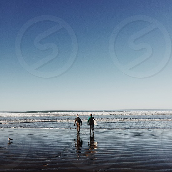 two people walking on beach carrying surfboard during daytime photo