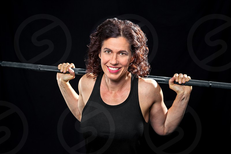 A smiling weight trainer poses for the camera with a barbell on her back.  She is on a black background and is cross lit. photo