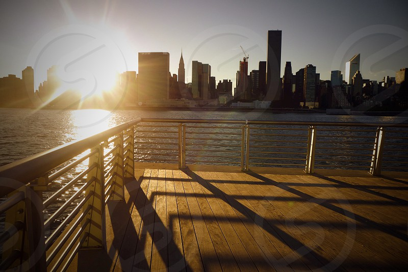 wooden balcony over river with view of city photo