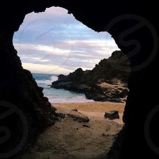 brown boulder near ocean photo