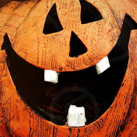 Close up of a smiling orange toy jack-o-lantern with three white teeth. photo