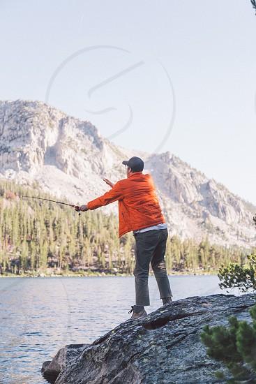 man wearing orange bubble jacket holding fishing rod near river photo