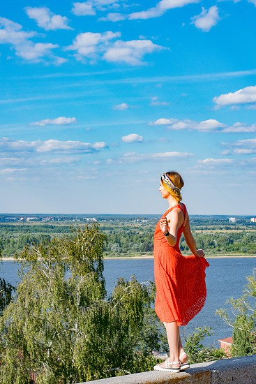A red hair adult young female model in a red summer dress posing on a high river bank looking away. photo