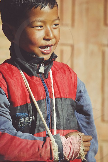 Young boy with a broken arm in a makeshift sling playing with friends in a Nepalese village outside of Kathmandu Nepal. photo