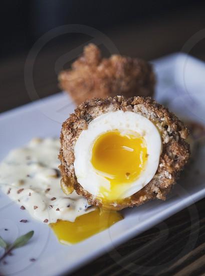 egg fried sausage scotch scotch egg meat sauce yolk runny photo