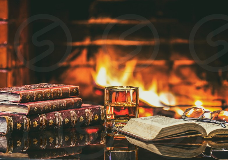 Glass of alcoholic drink wine and antique books in front of warm fireplace. Magical relaxed cozy atmosphere near  fire photo