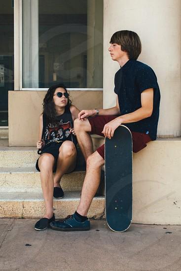 man sitting beside black skateboard photo