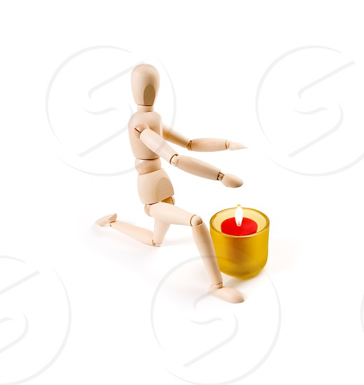 wood mannequin near a candle on white background photo