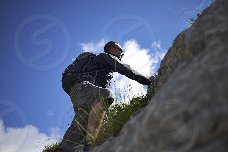 Caucasian man climbing up a rock in the Swiss mountains in summer sunshine photo