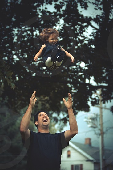 Father throwing his daughter up in the air  photo
