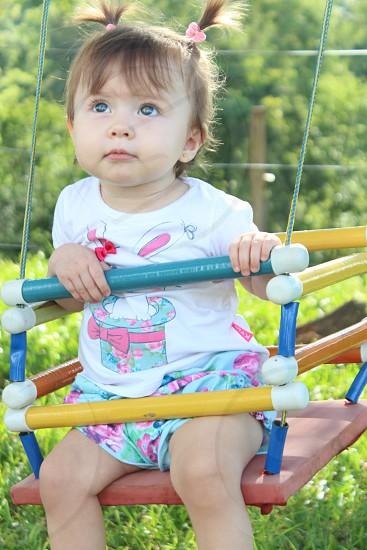 Criança brincando no balanço. Balançando no parque verde. (Child playing on the swing. Balancing on the green park) photo