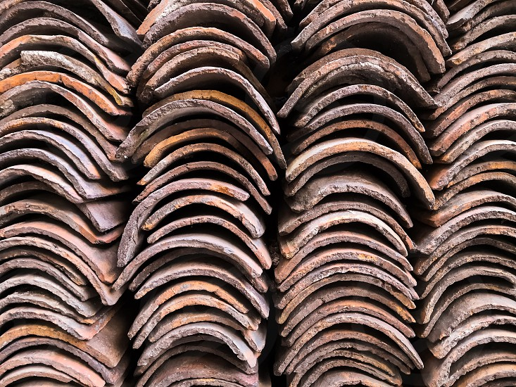 Abstract background of four columns of brown clay tiles stacked in a pile for traditional roof construction. photo