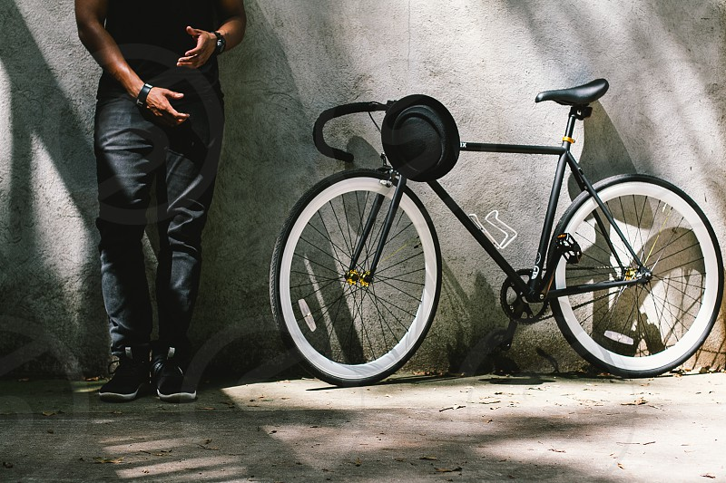 black hat on black bicycle near man photo