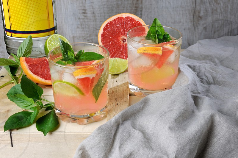 Cocktail from London dry gin with juice from squeezed red grapefruit and leaves of delicate basil of lemon lime slices and chilled ice cubes. photo