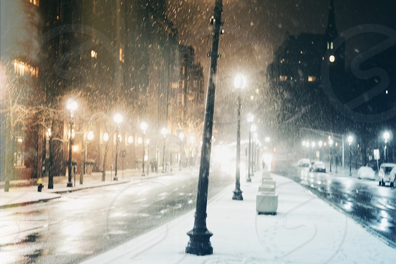 view of snowy street with lit street lamps at night photo