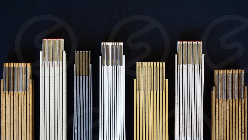A collection of old folding rulers lined up in a row of varying heights or measurements with both metric and English inch scales represented. photo