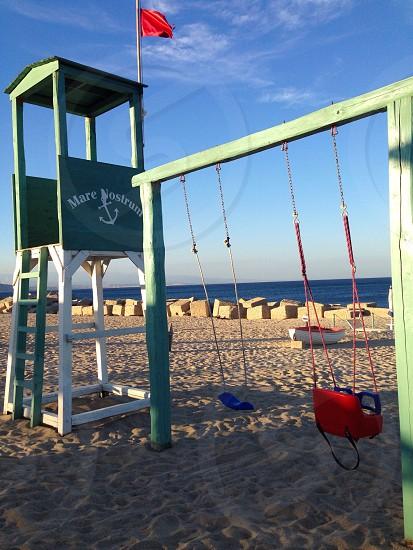 green painted swing set on beach photo