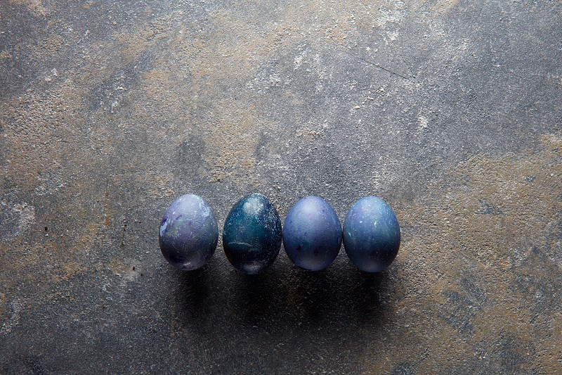 series of four Easter eggs on a dark background with space for text photo