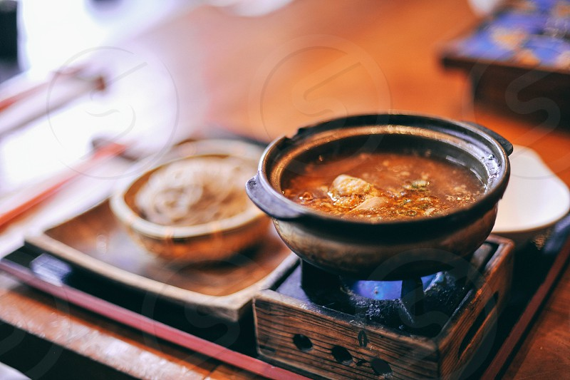 soup in bowl over burner beside pasta in brown wooden bowl on brown wooden tray photo