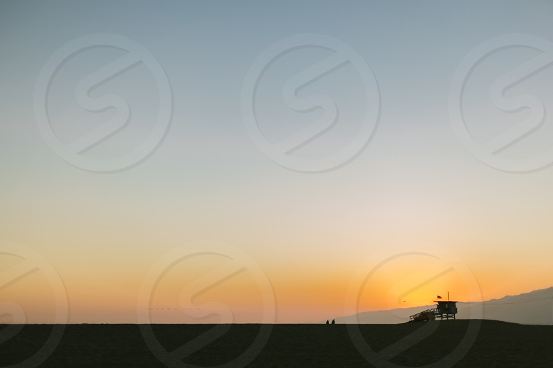 Sunset on Santa Monica Beach. A lifeguard tower and a small flock of birds silhouetted against the setting sun. photo