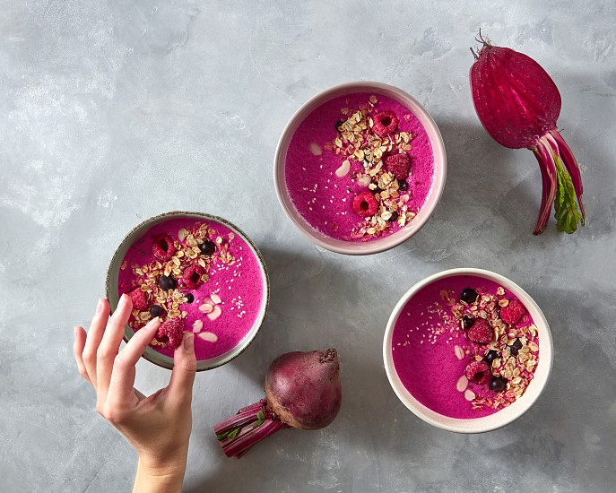 Beetroot smoothies with oatmeal and raspberry berries in a plate on a gray concrete background .The girl's hand puts raspberries in a plate. The concept of a healthy diet. Top view photo
