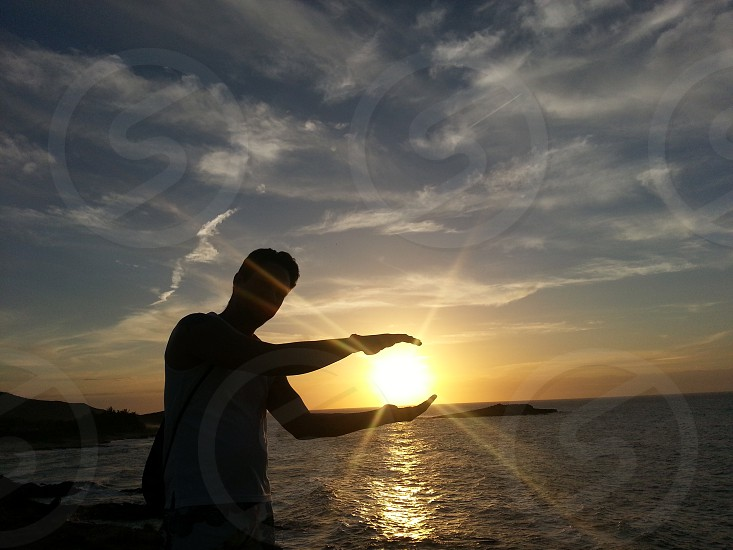 forced perspective photography of silhouette man standing near sea during sunset photo
