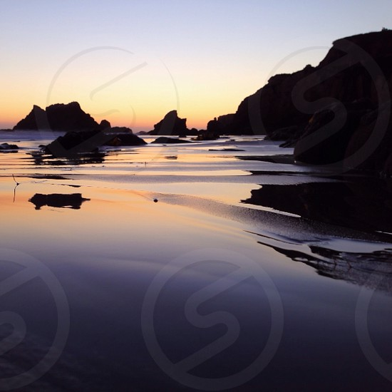 calm sea near the rocky shore in a sunset view photo