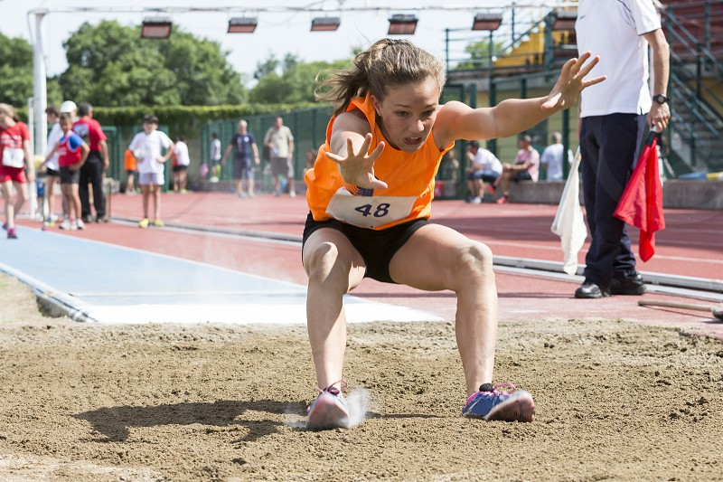 young woman performs the long jump photo