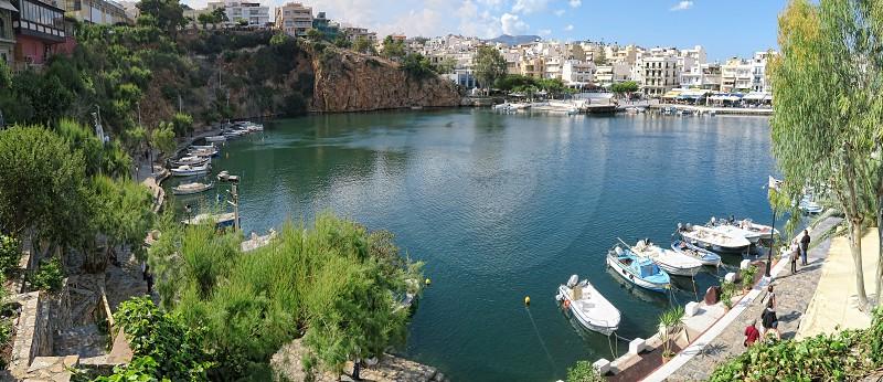 Agios Nikolaos Crete / GREECE May 22 2017: Cityscape of Agios Nikolaos with its Lake Voulismeni and harbor. (Crete) panorama of 5 images. photo