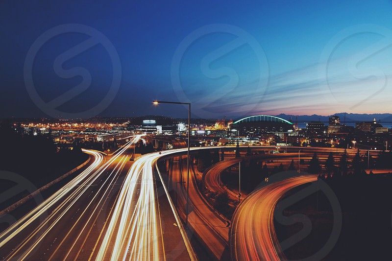 time lapse photography of cars passing by in highway during twilight near city photo