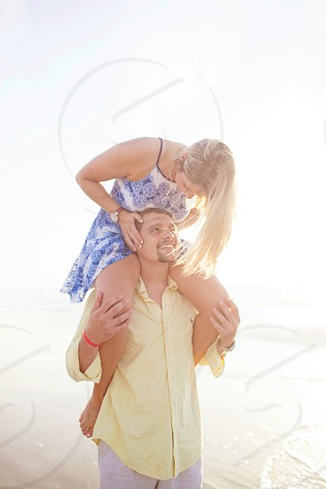 man in yellow button up dress shirt carrying woman in white and blue spaghetti strap dress during daytime photo