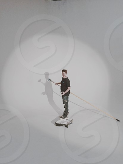 Young production assistant paints a cyclorama wall in a large all white photo studio.  photo