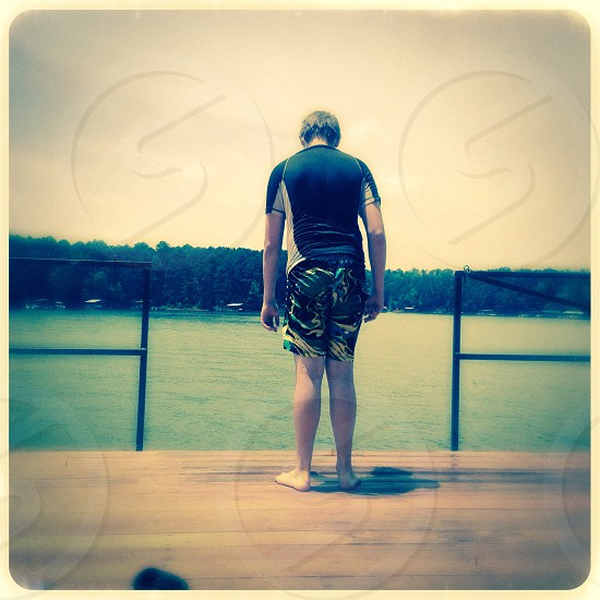 Boy on dock ready to jump photo